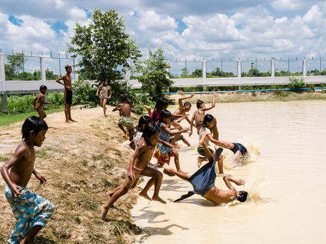 Khmer children play in the muddy watering hole that functions as their swimming pool at The Wat Opot Community, an orphanage for children affected by HIV and AIDS, near Chambak, Cambodia, outside Phnom Penh.