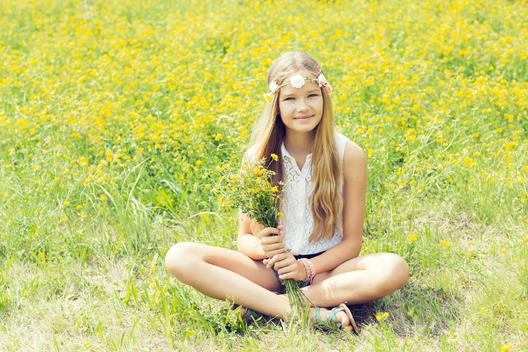 Portrait of a smiling girl sitting on a flower meadow wearing flowers