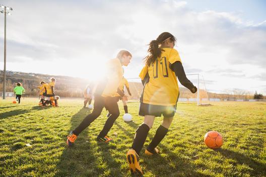 Girls practicing soccer drills on field