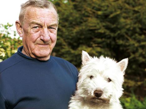 Portrait Of A Senior Man Holding His Dog.