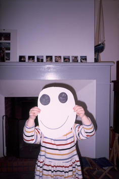 Child Hiding Behind Smiley Face Mask