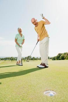 Spain, Mallorca, Senior couple on golf course, man cheering