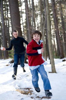 Father Throwing Snowballs And Chasing Son Through Woods