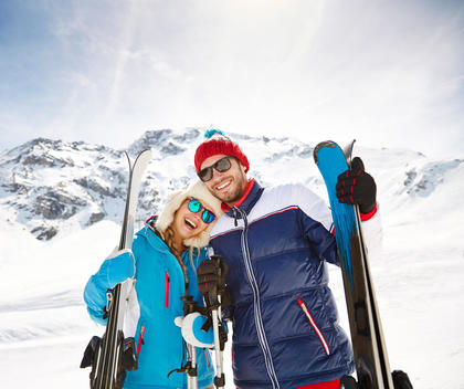 Couple carrying skis on mountain