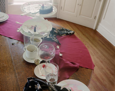 Wood Floor And Tabletop, White Plates And Dishes Littered With Dessert Remnants, Red Napkin, Glassware