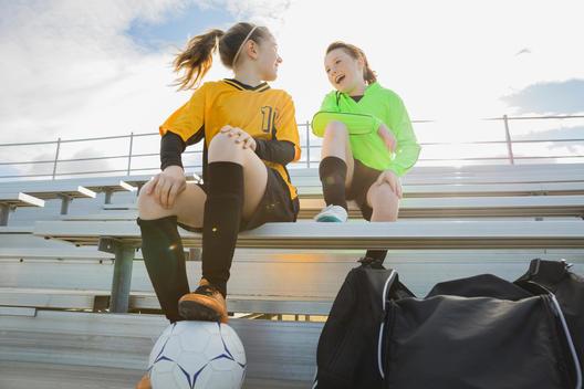 Girls in soccer uniforms sitting on bleachers