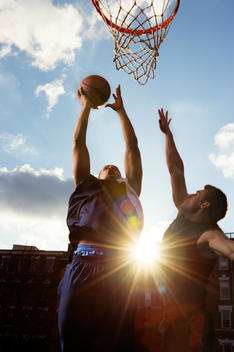 Two basketball players jumping for hoop on outdoor court