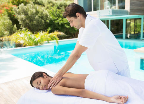Woman receiving massage poolside at spa