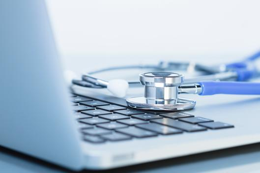 Cropped view of acoustic stethoscope on a laptop computer