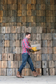 A farmyard. A stack of traditional wooden crates for packing fruit and vegetables. A man carrying an empty crate.