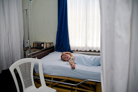 Young boy is laying down in a hospital room receiving a medicine drip to his body.