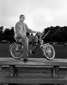 Pro BMX rider Dave Mirra sits on his bike on top of a picnic table