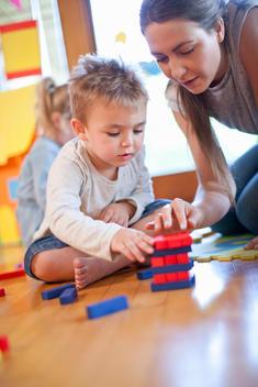 Teacher and boy constructing building blocks at nursery school