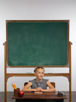 A well-groomed, young girl sits at a school desk in front of a chalkboard