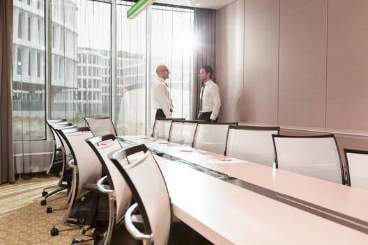 Poland, Warzawa, two businessmen talking at conference room in hotel