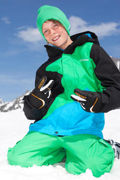 A cool kid wears a snowboard outfits and poses for the camera
