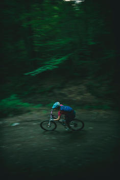 Young woman carving a downhill turn through a dark forest on a mountain bike.