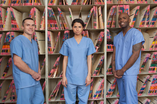 Nurses standing by shelves of medical records