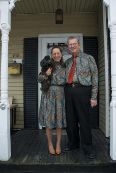 Portrait Of A Senior Couple With Their Poodle Standing On Their Front Porch