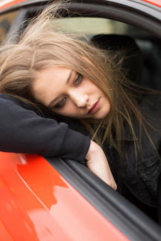 Blond girl head out window of red car hair blowing