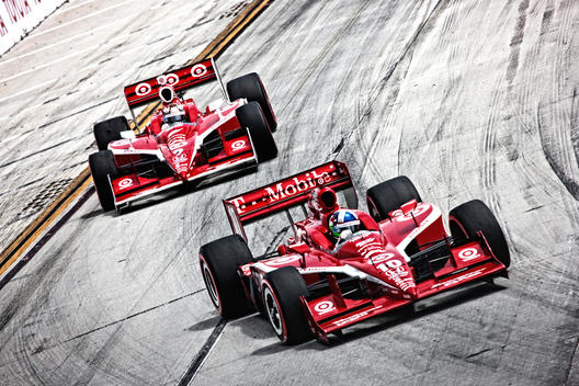Two red racecars turning a corner; Toyota Long Beach Grand Prix; Indycar racing; #9 & #10 cars