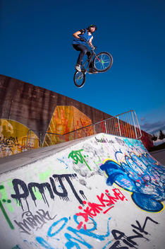 Germany, Young man performing stunt on BMX bike