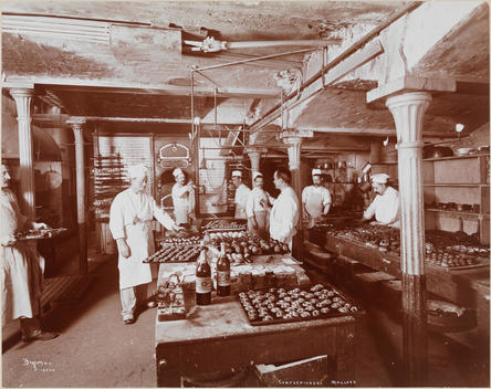 The Large, Industrial Kitchen At Maillard Confectionery Shows Eight Cooks Working And Large Trays Of Completed Cakes, Pastries And Other Baked Goods Cooling In Racks Or Displayed In Pans On Tops Of Tables.