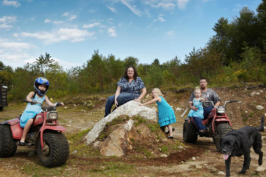 A Family Photo Of A Daughter Riding A Three-Wheeler, Mother Sitting On A Boulder, Another Daughter Climbing The Boulder And A Father Holding His Youngest Daughter While Sitting On A Three-Wheeler