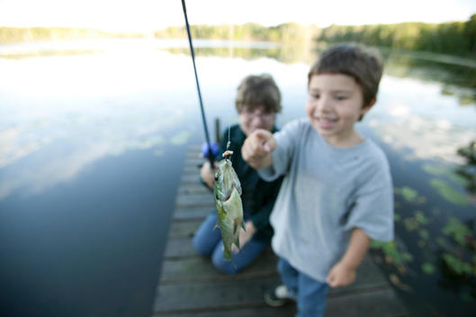 Mother And Son Fishing Together Off A Dock, Blue Lake, Minnesota, Usa.