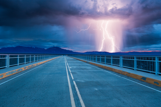 Rural New Mexico highway leading into thunderstorm over Sangre de Cristo Mountains, near Taos, conceptual composite.
