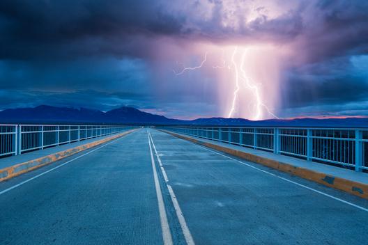 Rural New Mexico highway leading into thunderstorm over Sangre de Cristo Mountains, near Taos, conceptual composite.