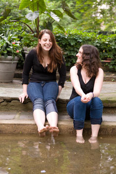 Two Sisters In The Garden Sitting By A Fountain Getting Their Feet Wet