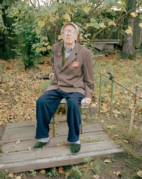 Elderly Man Decorated With Army Medals Sits On A Chair In His Garden Wearing His Slippers.