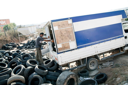 Turkish labor is loading truck with tyres .