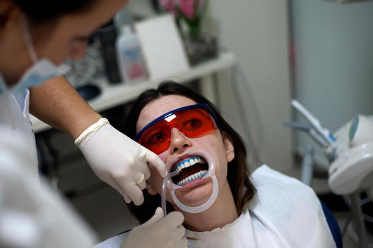Dental patient are getting her teeth whitening while that wearing a eye protecting glasses from the hazardous lights to dry the blue glues.
