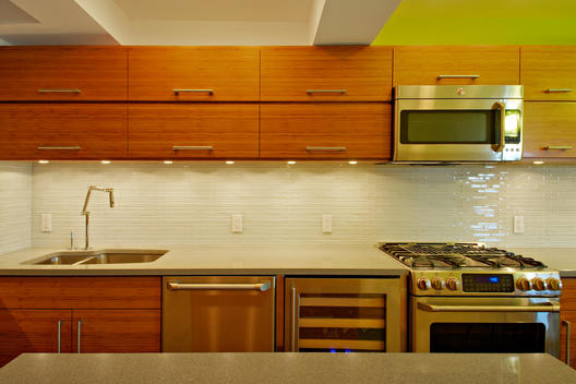 Ultra-Modern Green And Brown Kitchen With Pressed Molded Wood Cabinetry, Terrazzo Topped Island, Skinny-Tiled Wall, Stainless Appliances And Bent-Neck Sink Faucet