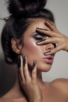 Beauty of a girl with eyeliner hair up off her face and her fingers dipped in black paint