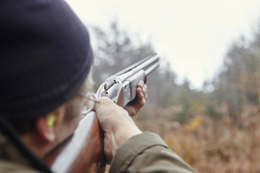 Man holding shotgun shooting clay pigeons