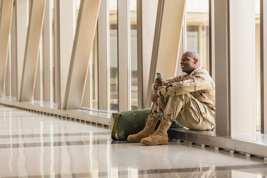 African American soldier using cell phone in airport