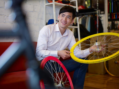 Young man in bike shop holding bicycle wheel