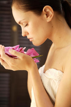 Portrait of a woman inhaling fragrant bright pink petals in her hands