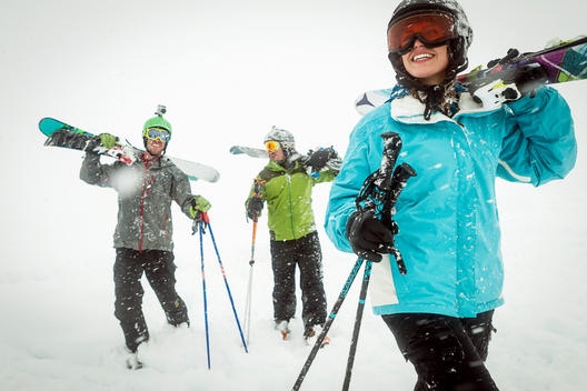 Group of skiers talking and walking to the slopes carrying their skis over their shoulders in near white-out snow conditions