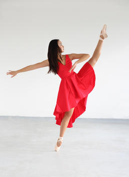 Dancer in red dress kicking into air