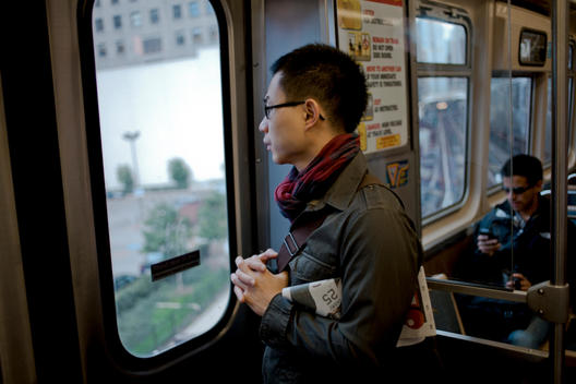 A Young Asian Man Looks Through Chicago Transit Train Windows On A Cloudy Afternoon.