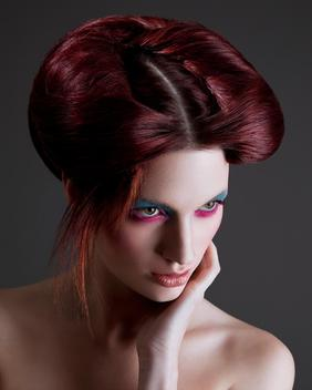 Portrait of young woman with heavy eye make-up and styled hair