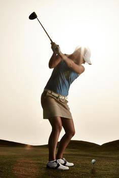 Woman swinging golf club