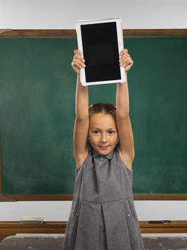 A school girl holds an electronic tablet up in the air above her head in front of a chalkboard