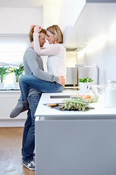 Couple hugging in kitchen, woman sitting on kitchen counter