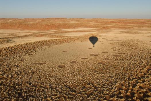 Shadow of hot air balloon over desert