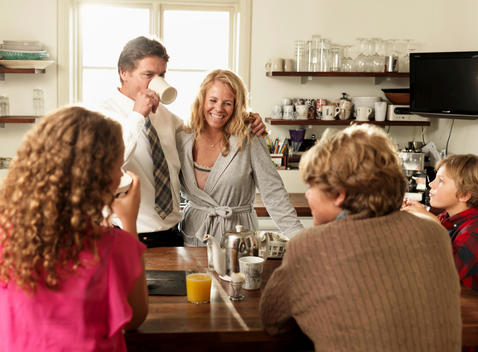 Family Sitting Together At Kitchen Table Over Breakfast